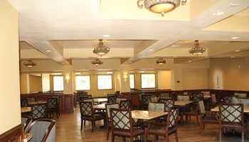 large dining room brightened by recessed lighting and small chandeliers.
