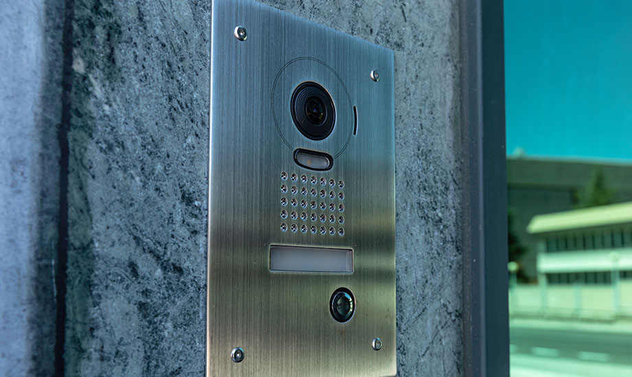 intercom at the door of a building with security camera