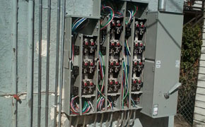 electrician working on panel with brakers